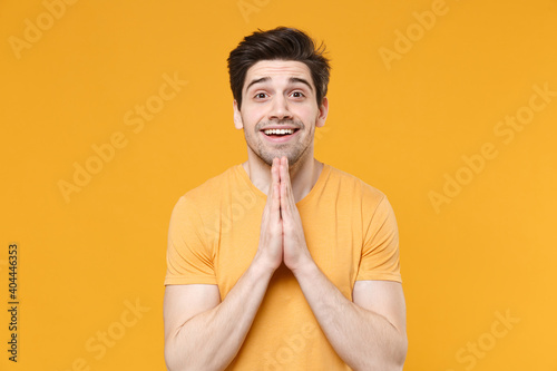 Obraz na plátně Young unshaved expecting caucasian handsome man 20s years old wearing casual basic blank print design t-shirt look camera holding hands in prayer isolated on yellow color background studio portrait