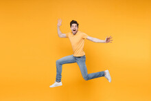 Full Length Side View Of Young Overjoyed Caucasian Excited Fun Surprised Man 20s Wearing Casual Basic T-shirt Jeans High Jumping Up Spreading Hands Isolated On Yellow Color Background Studio Portrait.