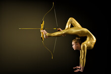 Archer Shooting By Legs With Gold Bow And Arrow. Flexible Gymnast Aiming Target Standing On Hand Upside Down. Goal Achievement Concept, Studio Shot Over Black Background