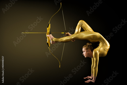 Fotografie, Obraz Archer Shooting by Legs with Gold Bow and Arrow