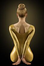 Woman Back Silhouette In Gold Dress. Perfect Slim Fit Body Rear View. Flexible Fashion Girl Model Backside. Bun Hair. Black Background
