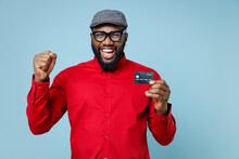 Joyful Young Bearded African American Man 20s Wearing Casual Red Shirt Eyeglasses Cap Standing Hold Credit Bank Card Doing Winner Gesture Isolated On Pastel Blue Color Wall Background Studio Portrait.