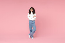 Full Length Young Smiling African American Woman 20s Curly Hair Wear White Casual Knitted Sweater Jeans Looking Camera Hold Hands Crossed Folded Isolated On Pastel Pink Background Studio Portrait.