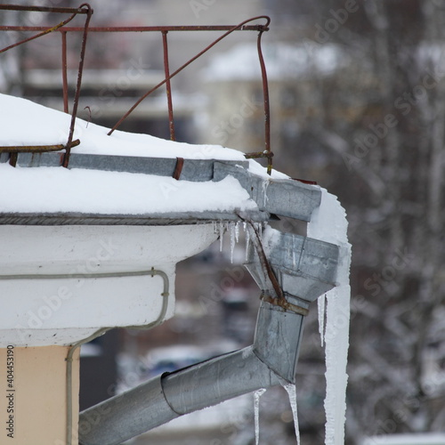 Obraz na plátně Drainpipe top with big icicles on snow covered old roof of residential house at