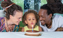 Birthday Party Of An Afro-descendant Child, African Father And Caucasian Mother Smile While The Young Boy Blows The Candle On The Chocolate Cake, Concept Of Multi-ethnic Family And Diversity