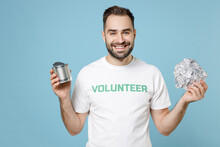 Smiling Cheerful Young Man In White Volunteer T-shirt Hold Foil Can Looking Camera Isolated On Blue Color Background Studio Portrait. Voluntary Free Assistance Help Trash Sorting Recycling Concept.