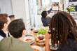 Leinwandbild Motiv Mann mit Freunden beim gemeinsamen Essen macht Videoanruf oder Selfie