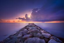 Rocky Jetty And Thunderstorm On The Horizon. Marina Di Cecina Beach, Tuscany, Italy.