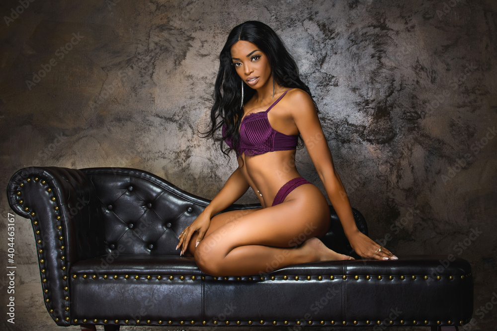 Fototapeta  Sexy young woman with long legs sitting on a dark brown leather sofa