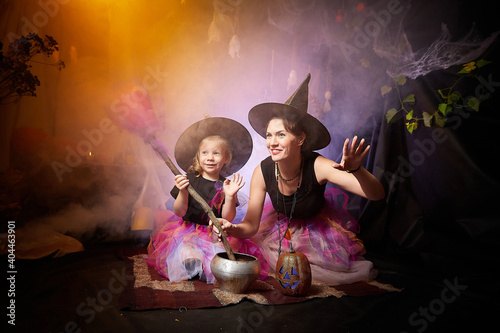 Beautiful brunette mother and cute little daughter looking as witches in special dresses and hats conjuring with a pot in room decorated for Halloween Fototapete