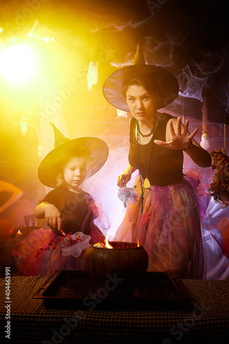 Fotografia, Obraz Beautiful brunette mother and cute little daughter looking as witches in special dresses and hats conjuring with a pot in room decorated for Halloween