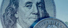 Close Uup One Hundred US Dollar And Coin With Description: Liberty. Selective Focus On Eyes Of Benjamin Franklin