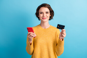 Portrait of positive cute bob hair girl hold smartphone credit card wear yellow pullover isolated on blue color background