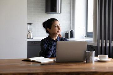 Fototapeta Fitness / Siłownia Dreamy young Indian woman sit at desk work on laptop look in distance thinking or visualizing. Happy thoughtful millennial ethnic female distracted from computer make plan or imagine success.