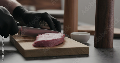 Foto man cut raw beef steak on oak board