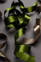 Vertical Image Of Curled Green And Brown Ribbon On The Grey Surface