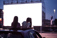 Rear View Of Two Female Friends Sitting In The Car While Watching A Movie In An Open Air Cinema With A Big White Screen