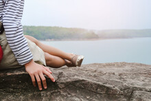 Low Section Of Woman Sitting On Rock Against Sky