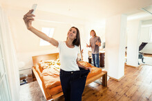 Smiling Woman In Loose Jeans Taking Selfie At Home