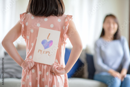 Fotografie, Obraz Asian cute girl hide handmade greeting card with i love mom word to give surpris