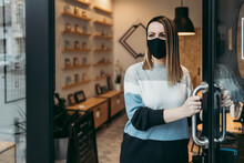 Young And Attractive Female Artist With Face Protective Mask Standing At Open Workshop Doors And Looking Outside. She Is Confident And Serious. Covid-19 Open For Business Concept.