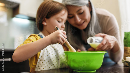 Fotografie, Obraz Granddaughter whipping in bowl while grandmother adding milk