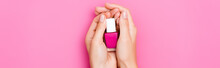 Top View Of Groomed Female Hands With Bottle Of Glossy Nail Polish On Pink Background, Banner