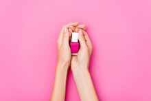 Cropped View Of Woman Holding Bottle Of Glossy Nail Polish On Pink Background