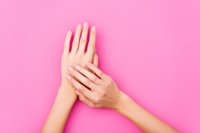 Top View Of Female Hands With Pastel Nail Polish On Fingernails On Pink Background