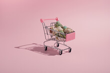 Creative Summer Composition Made Of Shopping Cart And Colorful Sea Shells On Pastel Pink Background. Minimal Concept.