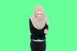 Leinwandbild Motiv Smiling Young Woman Wearing Hijab While Standing Against Green Background