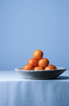 Close-up Of Oranges In Bowl On Table Against Wall