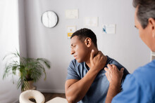 Injured African American Man Touching Neck Near Doctor On Blurred Foreground