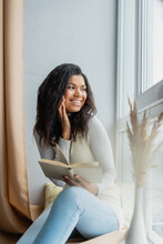 Cheerful African American Woman Looking Through Window While Sitting On Windowsill With Book