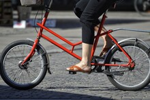 Low Section Of Woman Riding Bicycle On Footpath