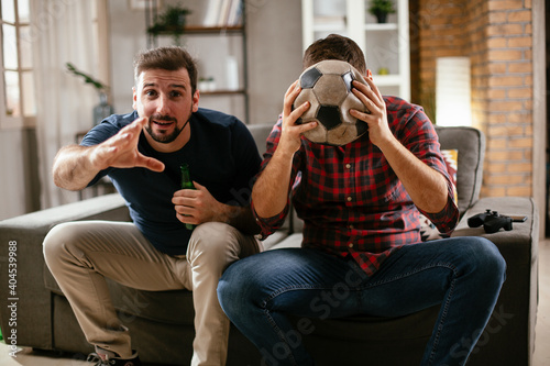 Obraz Two young friends enjoying at home. Men drinking beer and watching sports game on tv. - fototapety do salonu