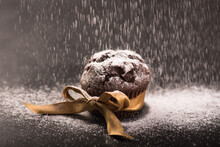 Close-up Of Homemade Chocolate Muffin With Gold Ribbon On A Dark Background On Which Falls Sugar.