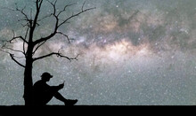 The Silhouette Of A Man Leaning Against A Dead Tree Looks At The Phone In Loneliness Against The Background Of The Stars And The Milky Way. Lonely Lonely Concept
