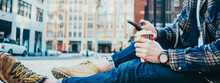 Man Sitting On The Street Sidewalk Resting With Cup Of Hot Coffee And Using Mobile Phone. Close-up. Wide Screen, Panoramic