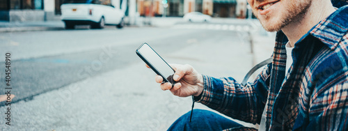 Casual man sitting on the street sidewalk resting with cup of hot coffee and talking on mobile phone using wireless earphones. Wide screen, panoramic