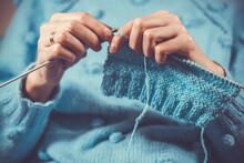 Close Up The Woman's Hands Knitting A Blue Woolen Sweater. Home Hobby