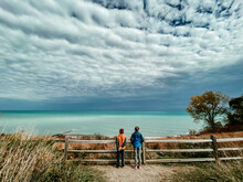 2 Boys Watching The Clouds On The Beach
