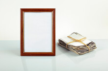 Blank Photo Frame For Photos, Flower In A Pot, Stack Of Old Photos On The Table. Mockup.