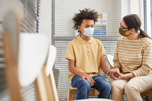 Portrait Of Caring Mother Comforting Son While Waiting In Line At Medical Clinic For Vaccination, Both Wearing Masks, Copy Space