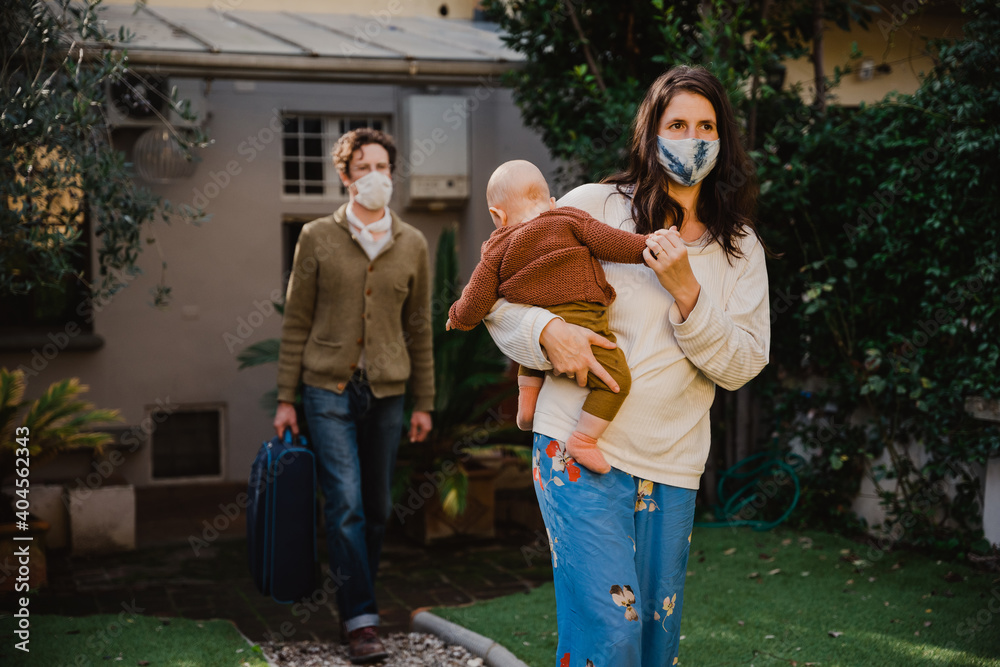 Fototapeta Young family with small child leaving their holiday accommodation - People wearing protective face masks against Covid-19 infections, Coronavirus, man carries suitcase while woman holds her child