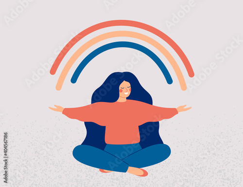 Fotografija Happy woman sits in lotus pose and open her arms to the rainbow