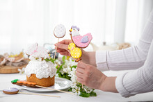 Women's Hands Decorate The Easter Cake With Festive Gingerbread On Sticks.