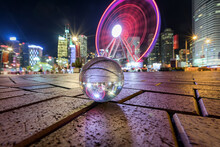 Reflection Of Illuminated Ferris Wheel In Crystal Ball At Night