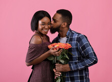 Affectionate Black Guy Giving His Sweetheart Bouquet Of Flowers For Valentine's Day And Kissing Her On Pink Background