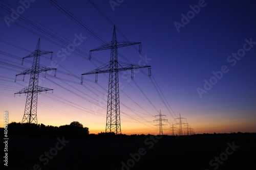 Obraz na plátně Low Angle View Of Silhouette Electricity Pylon On Field Against Romantic Sky